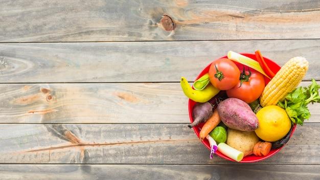 Hohe winkelsicht des gesunden gemüses in der schüssel auf hölzerner planke