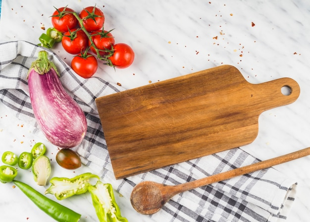 Hohe winkelsicht des gesunden gemüses mit hölzernem schöpflöffel und copping board in der küche