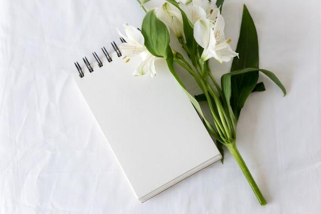 Hohe winkelsicht des gewundenen notizblockes mit weißen lilien blühen über weißem hintergrund