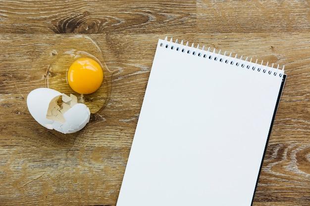 Hohe winkelsicht des gewundenen notizblockes und des eies auf hölzernem schreibtisch
