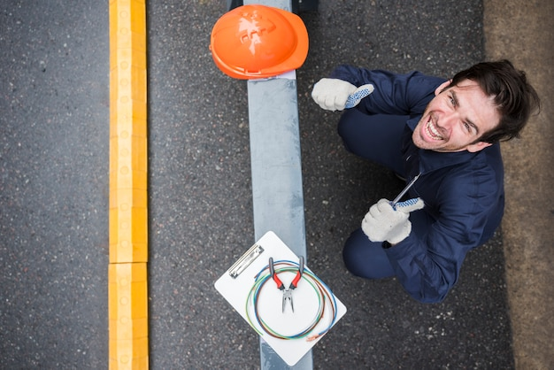 Hohe winkelsicht des glücklichen männlichen elektrikers, der sich daumen am arbeitsplatz zeigt
