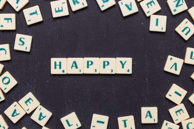 Hohe winkelsicht des glücklichen wortes mit scrabblebuchstaben