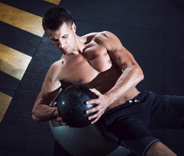 Hohe winkelsicht des jungen mannes des sitzes, der mit medizinball trainiert