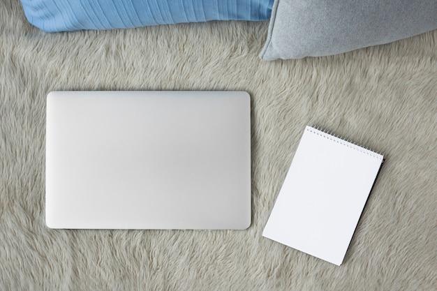 Hohe winkelsicht des laptops und des gewundenen notizblockes auf sofa
