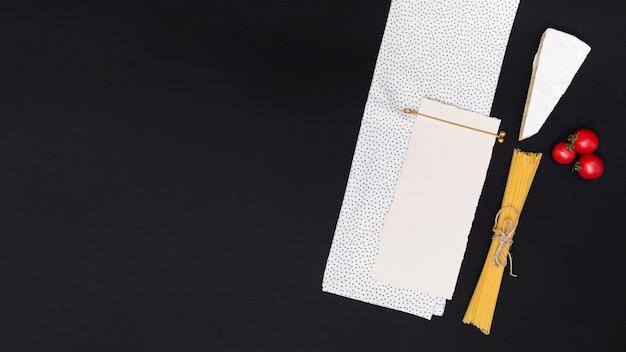 Hohe winkelsicht des leeren papiers und der serviette mit ungekochtem spaghettiteigwarenbestandteil