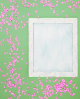 Hohe winkelsicht des leeren rahmens mit rosa konfettis gegen grünen hintergrund