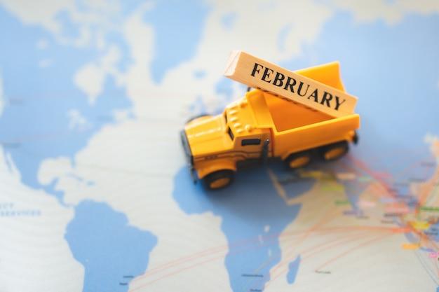 Hohe winkelsicht des lkw-fahrzeugs holzblock im februar auf unscharfem kartenhintergrund anhebend