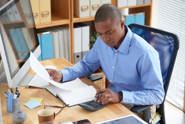 Hohe winkelsicht des männlichen buchhalters finanzdokument überprüfend