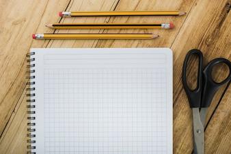 Hohe Winkelsicht des Notizblockes; Schere und Stifte auf hölzernen Hintergrund