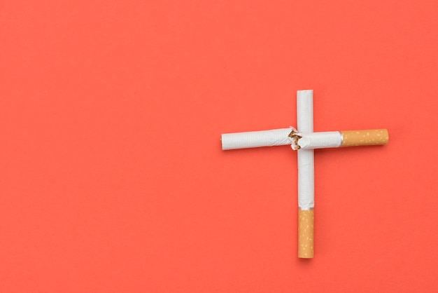 Hohe winkelsicht des querzeichens gemacht von der zigarette auf orange hintergrund