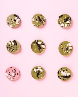 Hohe winkelsicht des rosa runden nachtischs unter grünen nachtischen vereinbarte in der reihe auf hintergrund