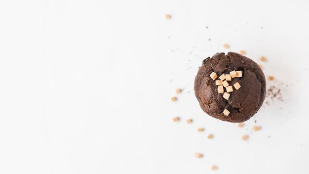 Hohe winkelsicht des schokoladenkleinen kuchens mit karamellsüßigkeitsspitzen auf weißem hintergrund