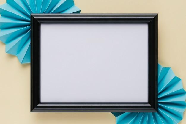 Hohe winkelsicht des schwarzen hölzernen grenzfotorahmens mit blauem origamifan auf beige hintergrund