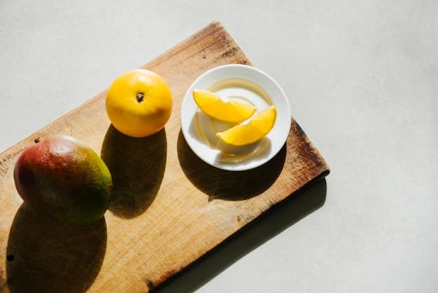 Hohe winkelsicht des süßen kalkes und der mango auf schneidebrett