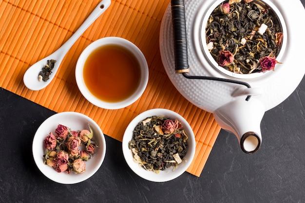 Hohe winkelsicht des trockenen krauts in der keramischen schüssel mit teekanne