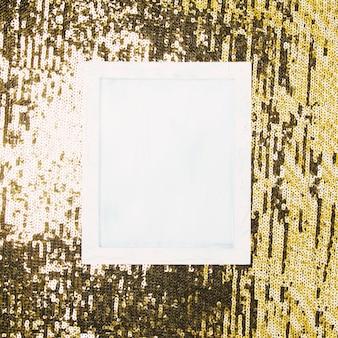 Hohe winkelsicht des weißen leeren rahmens über glänzendem paillettehintergrund