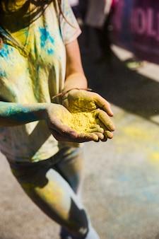 Hohe winkelsicht einer frau, die in der hand gelbe farbe hält