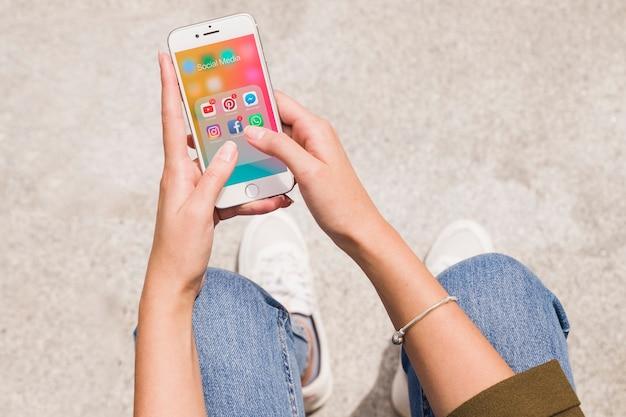 Hohe winkelsicht einer frau, die social media-app auf mobiltelefon verwendet