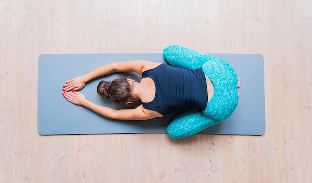 Hohe winkelsicht einer frau, die übung auf yogamatte tut