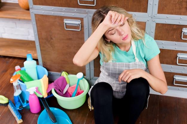 Hohe winkelsicht einer überarbeiteten reinigungsfrau, die auf boden mit reinigungswerkzeugen und -produkten sitzt