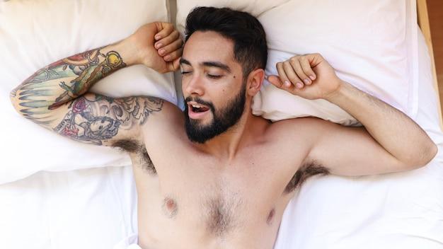 Hohe winkelsicht eines hemdlosen jungen mannes, der auf bett schläft
