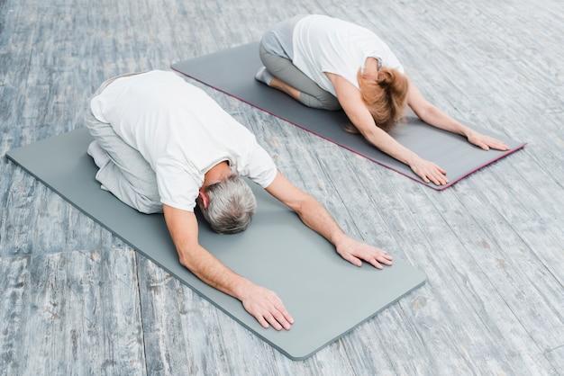 Hohe winkelsicht eines paares in der weißen ausstattung, die yoga-positionen ausdehnend übt