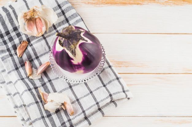 Hohe winkelsicht von auberginen- und knoblauchzehen auf kariertem musterstoff über hölzerner planke