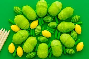 Hohe Winkelsicht von Bleistiften und von verschiedenen süßen Süßigkeiten auf grünem Hintergrund