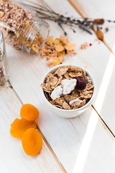 Hohe winkelsicht von cornflakes in der schüssel nahe verschüttetem granola und in den trockenen früchten auf hölzerner planke