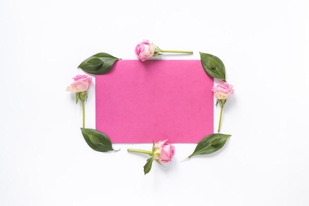 Hohe winkelsicht von den blumen und von blättern, die leeres rosa papier auf weißer oberfläche umgeben