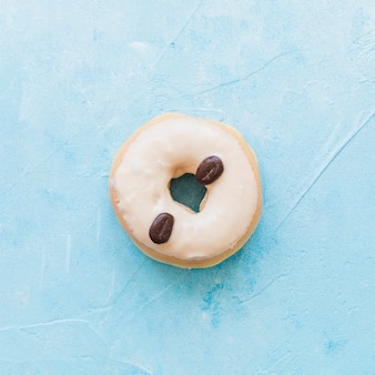 Hohe winkelsicht von den schaumgummiringen verziert mit kaffeebohnen auf blauem hintergrund