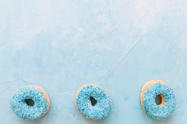 Hohe winkelsicht von geschmackvollen schaumgummiringen auf blauer oberfläche