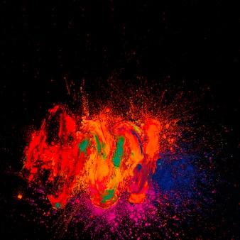 Hohe winkelsicht von hellem holi gefärbt vor schwarzem hintergrund