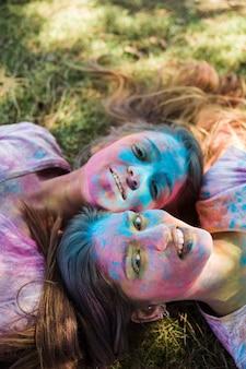 Hohe winkelsicht von jungen frauen mit holi farbe auf ihrem gesicht, das auf dem rasen betrachtet kamera liegt