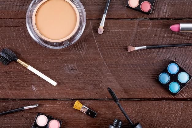 Hohe winkelsicht von kosmetischen produkten mit bürsten auf hölzernem hintergrund