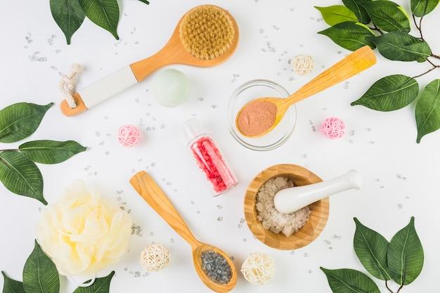 Hohe winkelsicht von kosmetischen produkten und von grünblättern auf weißem hintergrund