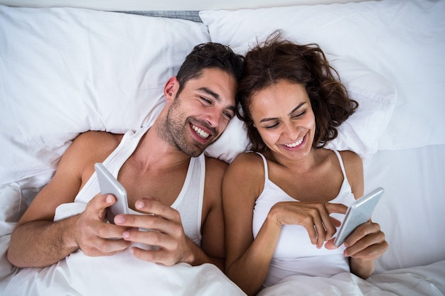 Hohe winkelsicht von lächelnden paaren unter verwendung des smartphone auf bett