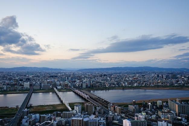 Hohe winkelsicht von osaka-stadt mit dem yodo zur sonnenuntergangzeit in der kansai-region vom umeda-himmelgebäude