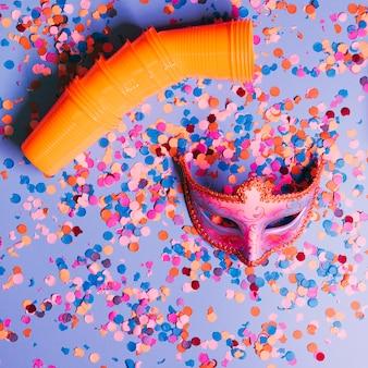 Hohe winkelsicht von plastikgläsern und von eleganter parteimaske mit konfetti auf blauem hintergrund