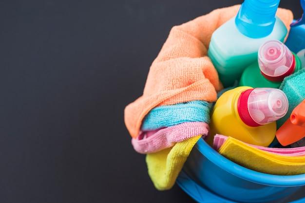 Hohe winkelsicht von reinigungsprodukten im korb über schwarzem hintergrund
