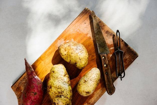 Hohe winkelsicht von rohen kartoffeln auf hölzernem schneidebrett