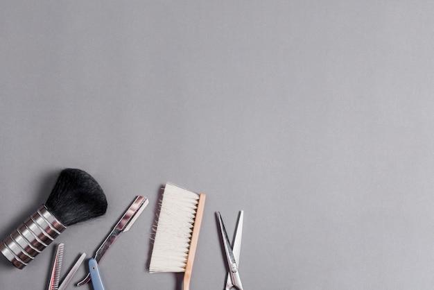Hohe winkelsicht von verschiedenen friseurwerkzeugen über grauem hintergrund