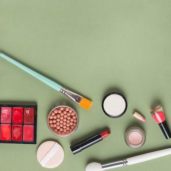 Hohe winkelsicht von verschiedenen make-upprodukten auf grünem hintergrund