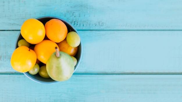 Hohe winkelsicht von verschiedenen saftigen früchten in der schüssel auf die blaue holztischoberseite