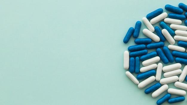 Hohe winkelsicht von weißen und blauen süßigkeitskapseln auf grünem hintergrund