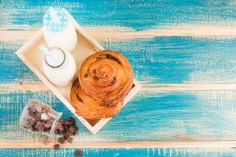 Hohe Winkelsicht von Zimtbrötchen- und Milchflaschen im hölzernen Behälter nahe verschütteten choco Chips vom Glasgefäß