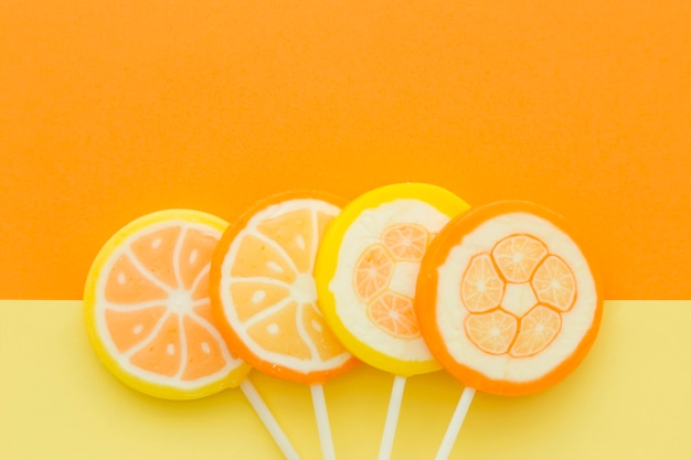 Hohe winkelsicht von zitrusfruchtsüßigkeiten auf gelbem und orange hintergrund