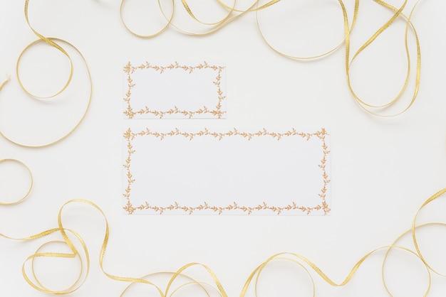 Hohe winkelsicht von zwei leeren karten umgeben mit bändern auf weißer oberfläche
