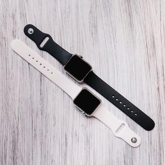 Hohe winkelsicht von zwei schwarzweiss-smartwatch