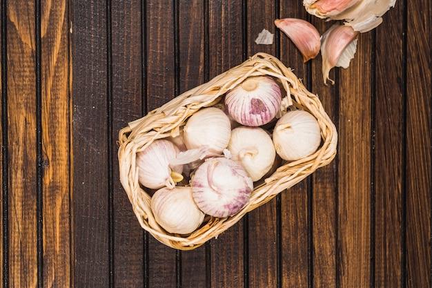 Hohe winkelsicht von zwiebeln im korb nahe knoblauchzehen auf hölzernem hintergrund